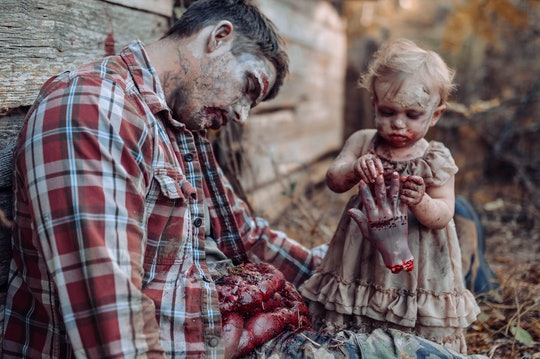 A zombie baby eats the hand of her father during a photoshoot.