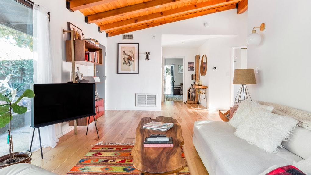 A spacious living room with hardwood floors and vented ceilings, a white couch with fluffy white pillows, and wooden furniture.