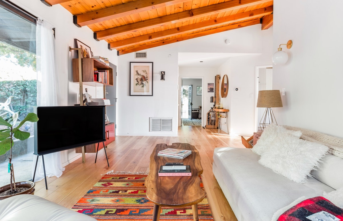 A spacious living room features hardwood floors, a white couch with fluffy white pillows, and wooden furniture.