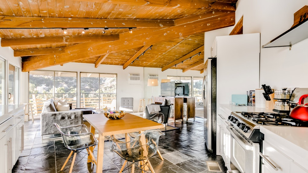 A giant open loft, with a dining table, kitchen, and living room visible, with floor to ceiling windows overlooks the Hollywood Hills.