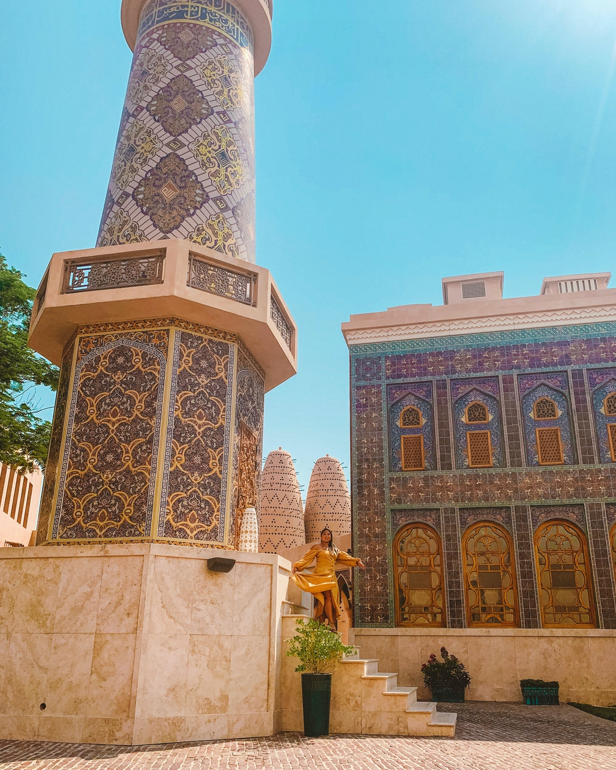 A woman in a brown dress walks down the steps of a purple, blue, and green mosque.