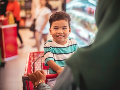 A little boy sitting in a shopping cart while his mom pushes him through the store.
