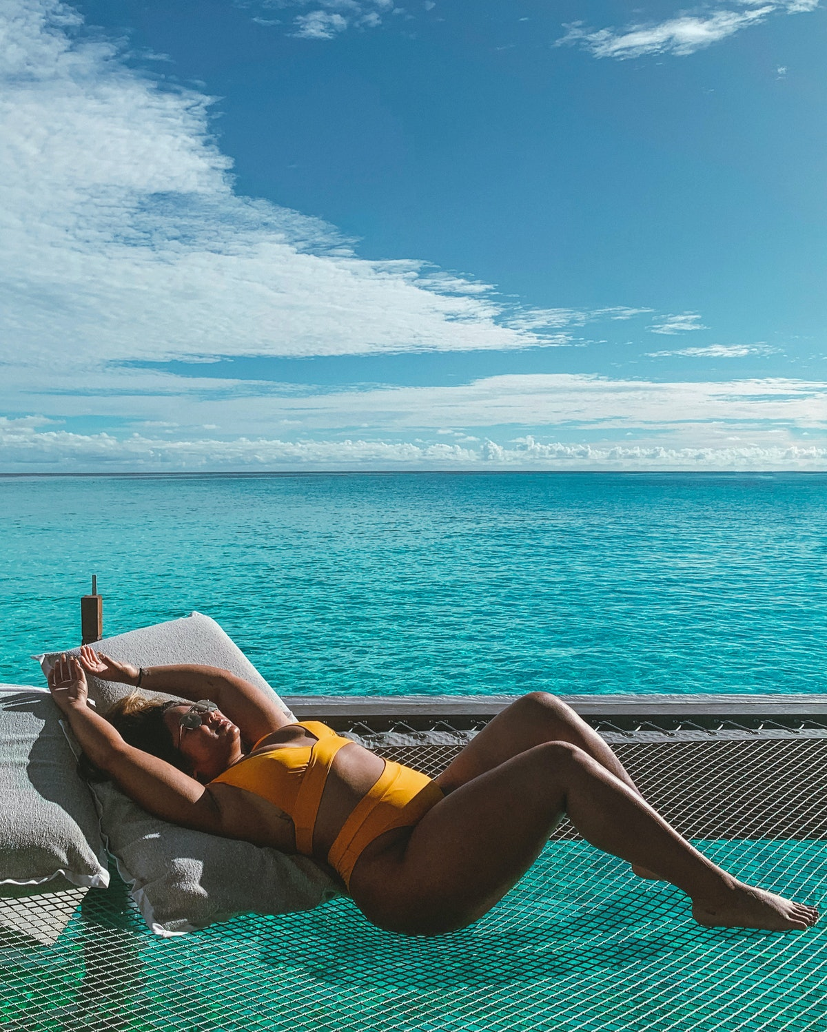 A woman in an orange high-waist bikini relaxes on an over-water net, overlooking a turquoise ocean with a blue sky in the background.