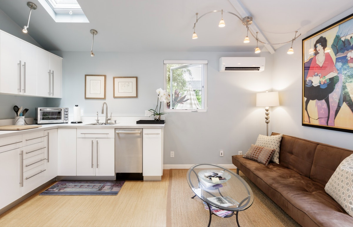 An open floor map of a white kitchenette on the left side and a brown couch and oval glass coffee table on the right side.