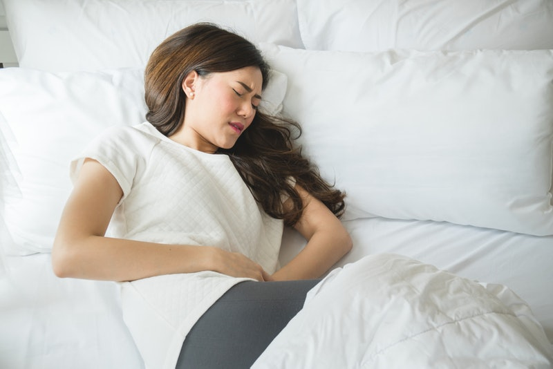 A woman in bed holding her bloated stomach, wondering if she's passing gas too often.