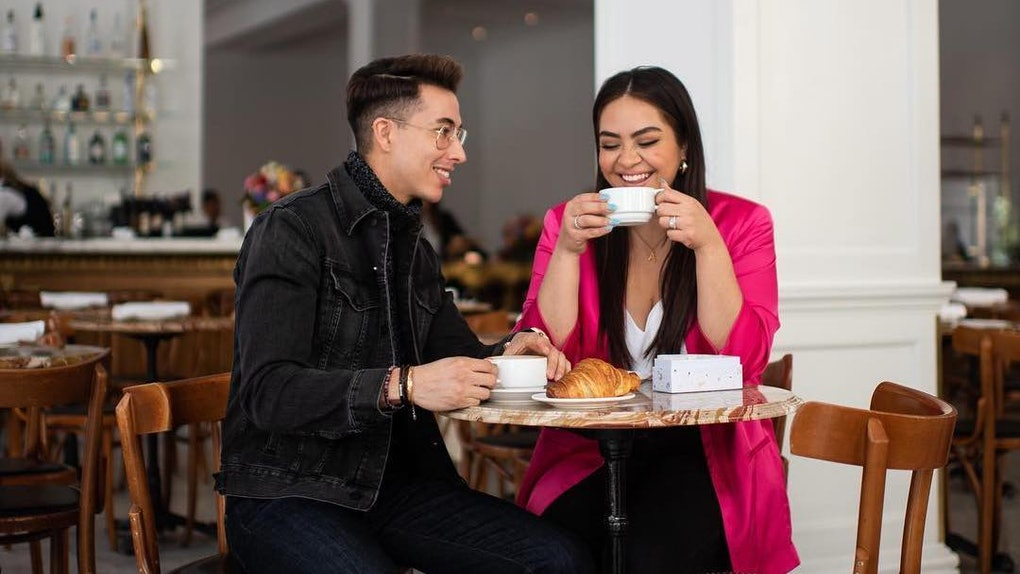 A young couple enjoys coffee and croissants at a small bistro-like table in an empty restaurant.