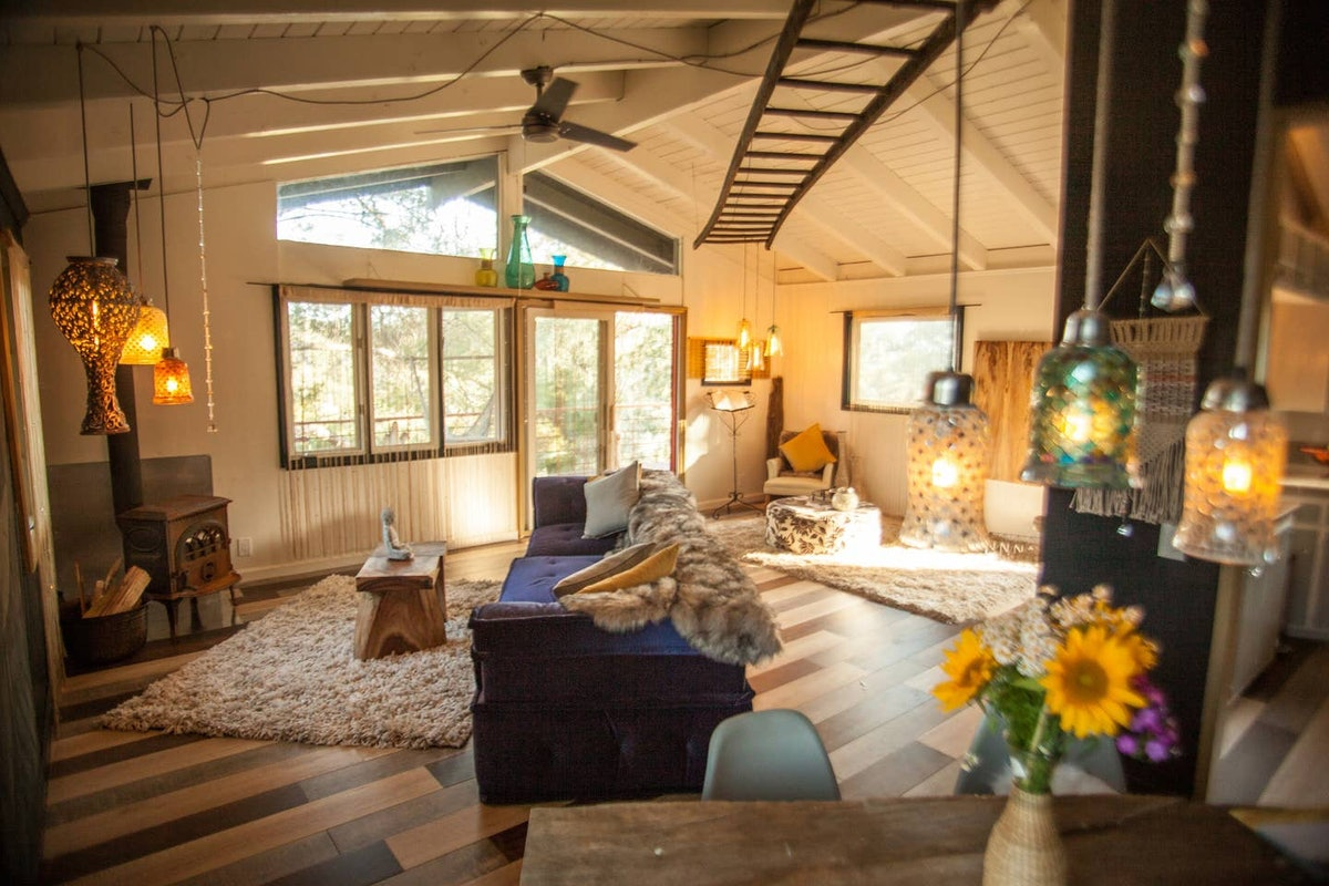 A boho-inspired living room decorated with lots of hanging lights and a ladder on the ceiling.