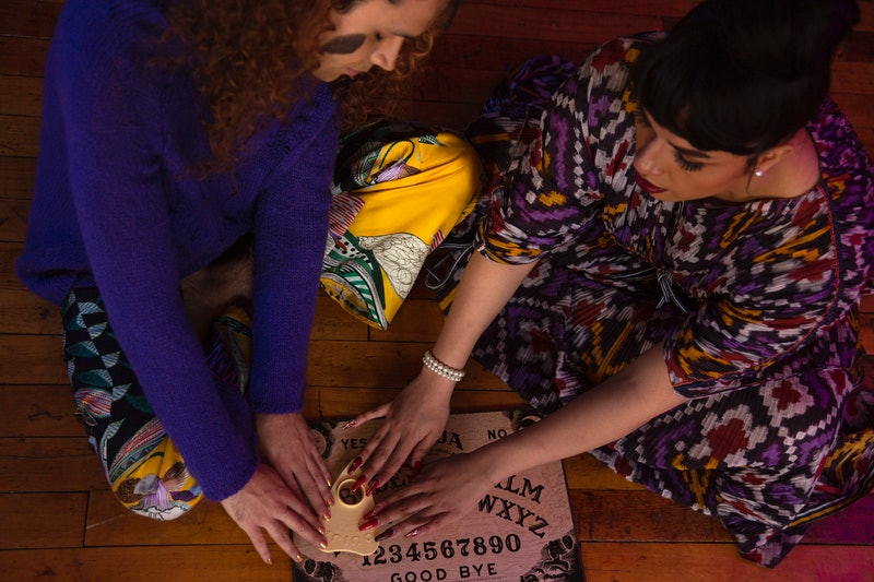 Two people use a Ouija board. For trans and nonbinary folks, Halloween can be a valuable time to play with gender.