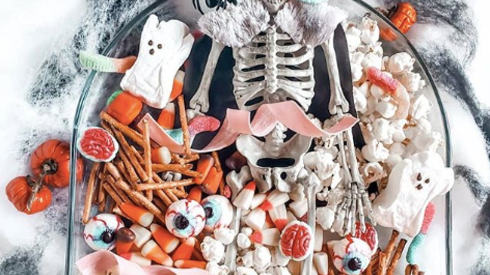 This candy Halloween charcuterie board features spooky treats like candy eyeballs and gummy worms with plastic spiders, candy pumpkins, and popcorn.