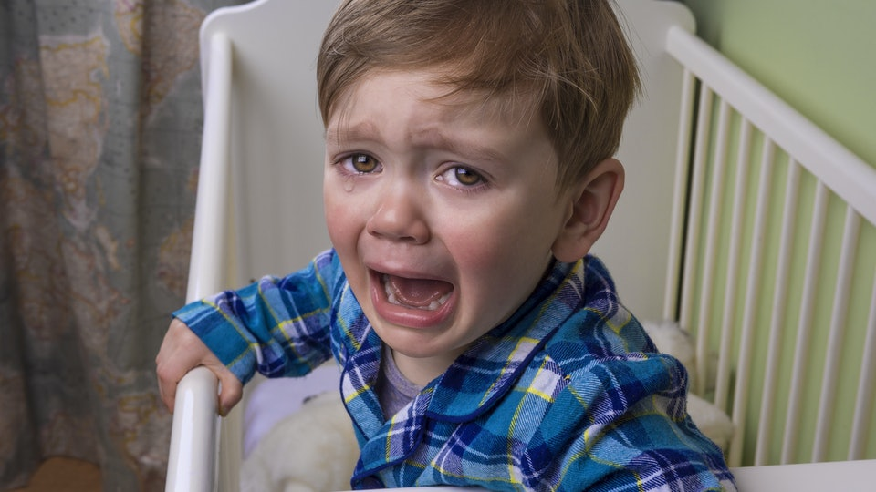 Toddler-aged child crying in crib.