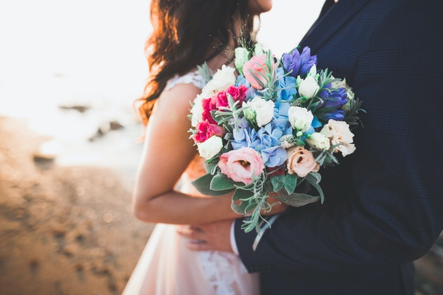 Bride carrying colorful wedding bouquet