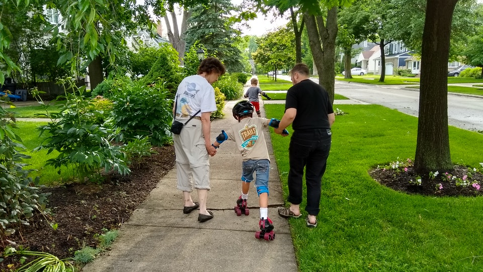A grandmother helps her grandchildren learn to roller skate.