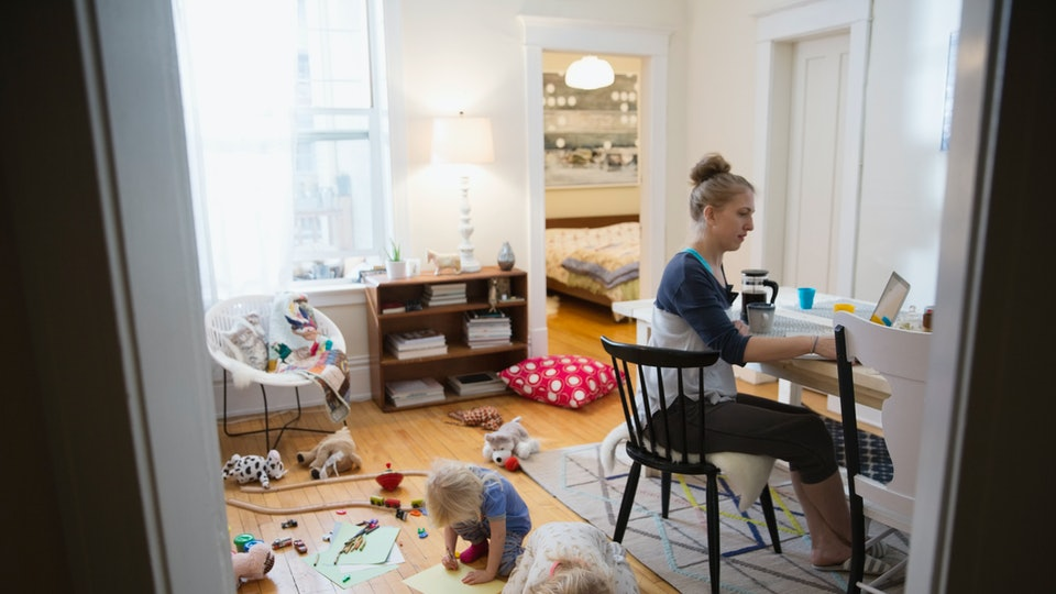 woman working on laptop as two children play on floor