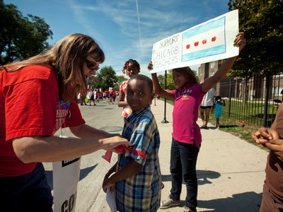 Karen Rieck, a teacher at Faraday Elementary School, greets her students as they show support for public school teachers rallying on in West Chicago in 2012.