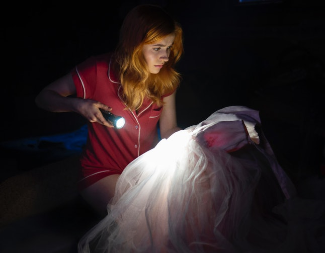 Nancy looking at Dead Lucy's dress on Nancy Drew