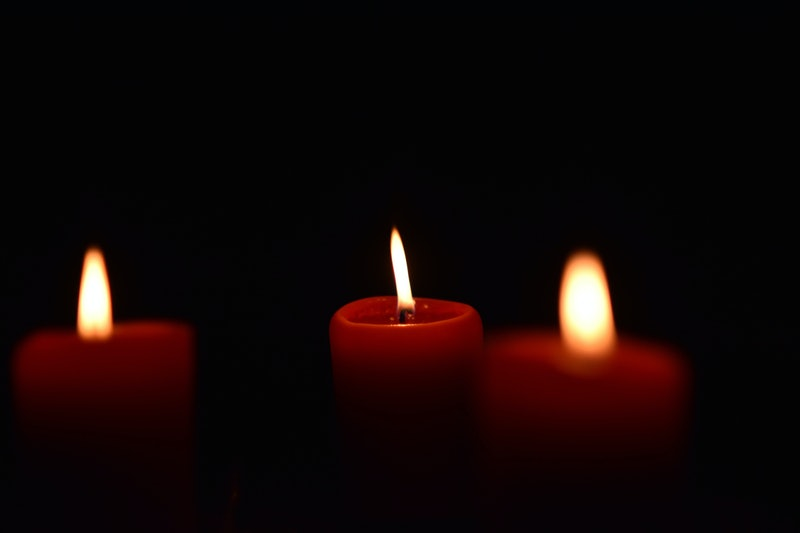 Red candles burn against a black backdrop in this story about witchcraft, books, and witches of color.