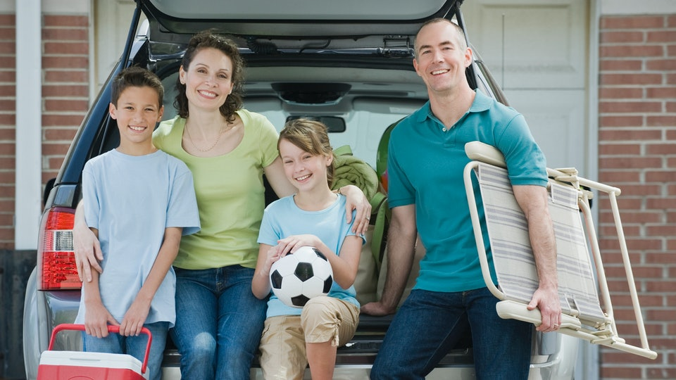 mom, dad, and two kids in soccer uniforms sit in back of car.