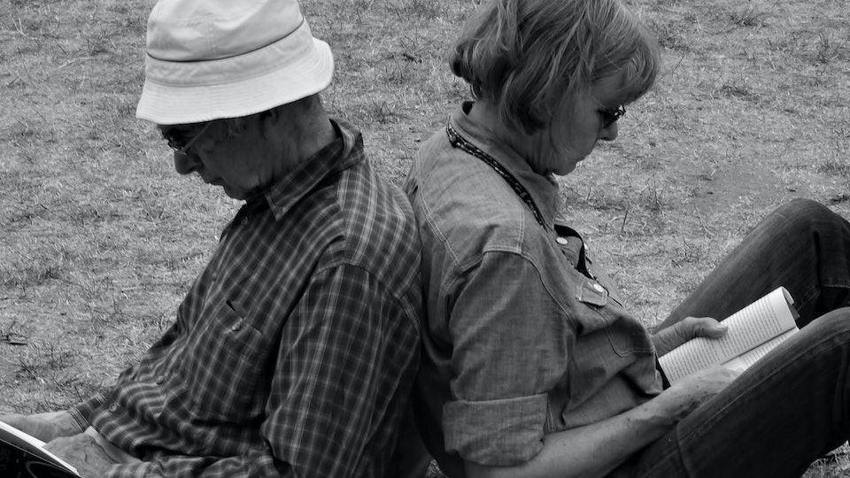 Elderly couple reading books back to back