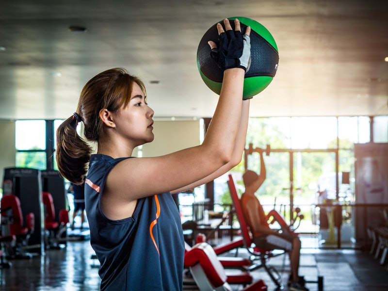 A person in a gym stands with a medicine ball in her hands. If spending your free time in the gym is...