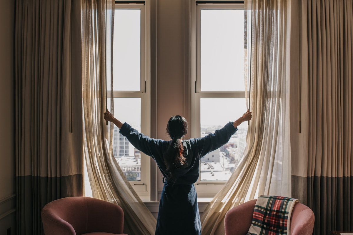 A woman in a bathrobe with her back turned to the camera opens up the curtains in her room.