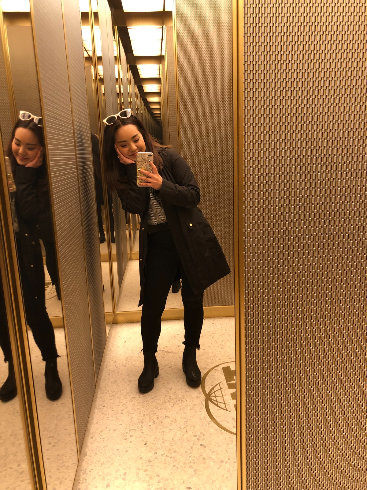 A woman with white sunglasses on her head wearing a long black coat, black jeans, and black boots takes a selfie in an elevator mirror.