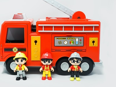 Ryan's World Mystery Fire Truck: Three toy figurines standing in front of a red fire truck
