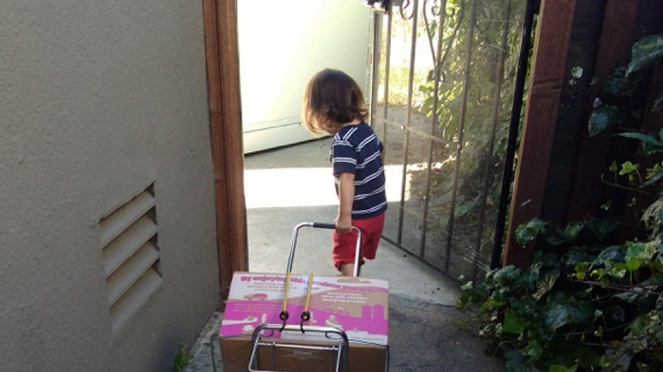A picture of a young child pulling a cart behind them as they exit their home.