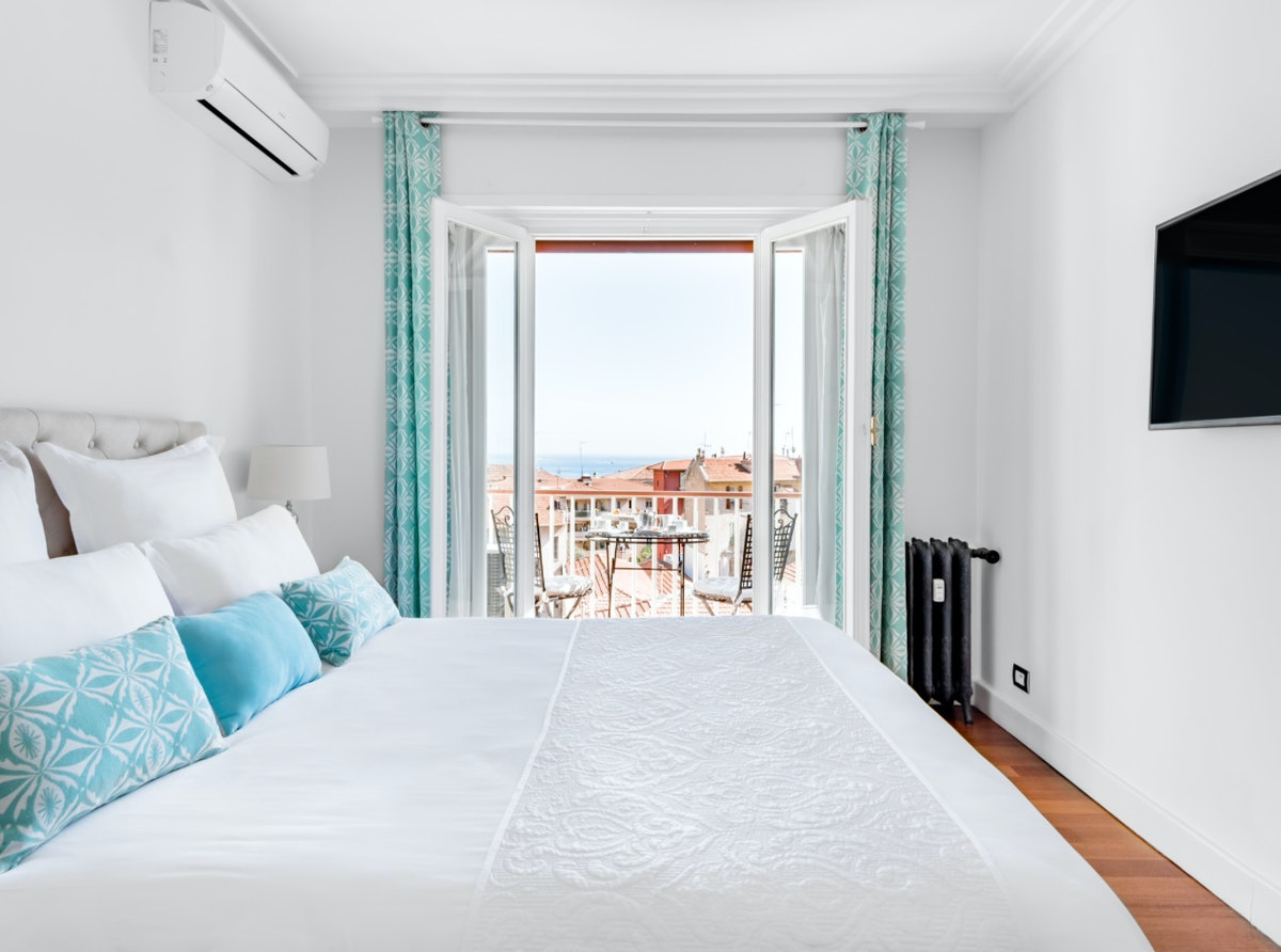 The bedroom of an apartment in Beaulieu-sur-Mer is very bright and has a gorgeous view of the ocean and town.