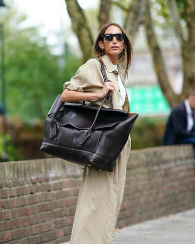 Street style photo of influencer Chloé Harrouche carrying an oversized Bottega Veneta bag at London Fashion Week Spring 2020.
