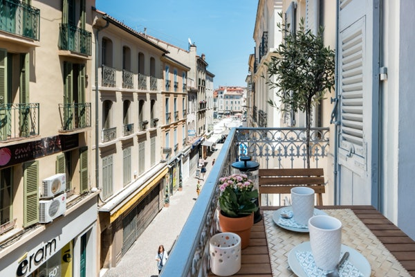 The balcony of an Airbnb in the French Riviera has beautiful views of the colorful buildings and neighborhood streets.