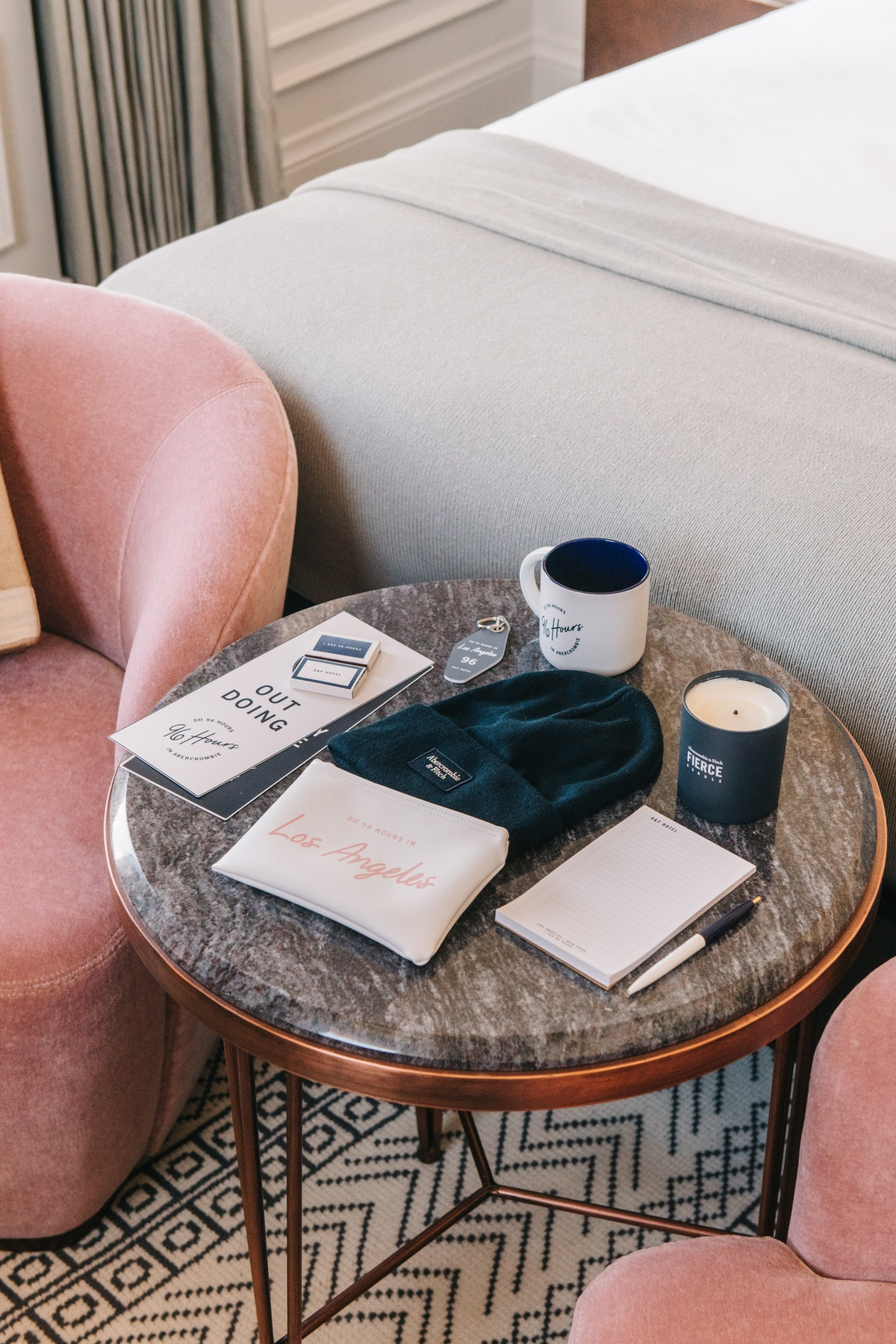 A dark marble coffee table with staycation products — like an itinerary, beanie, candle, toiletry po...