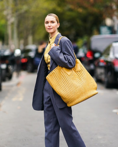 Street style photo of influencer Pernille Teisbaek carrying an oversized Bottega Veneta bag at Paris Fashion Week Spring 2020.