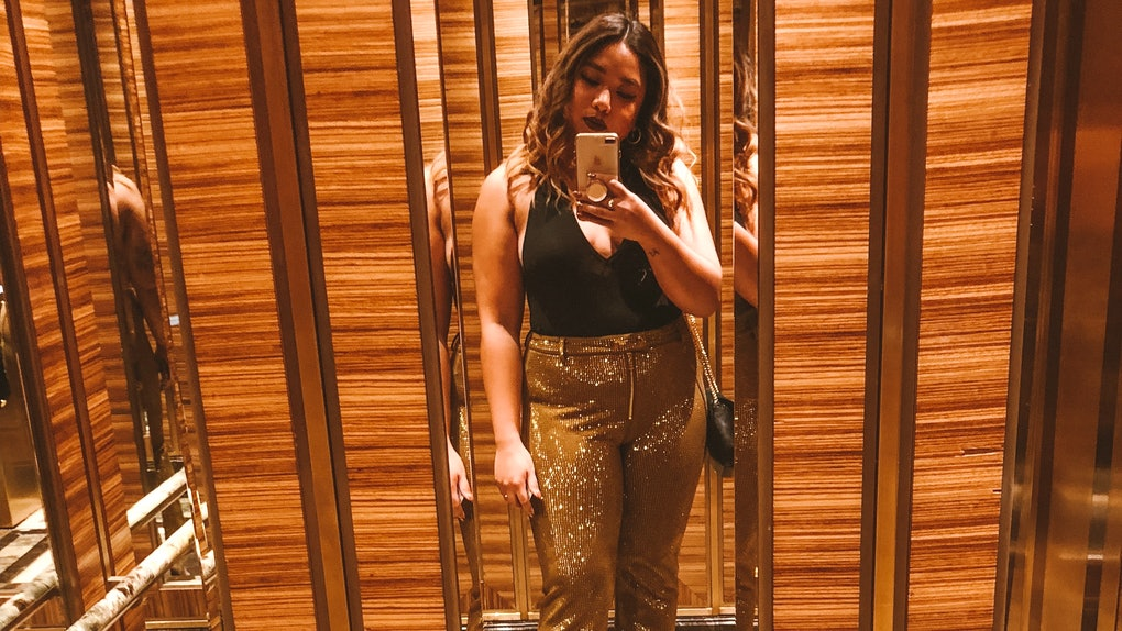 A woman in a black halter top and sparkly gold pants takes a phone selfie in an elevator mirror.