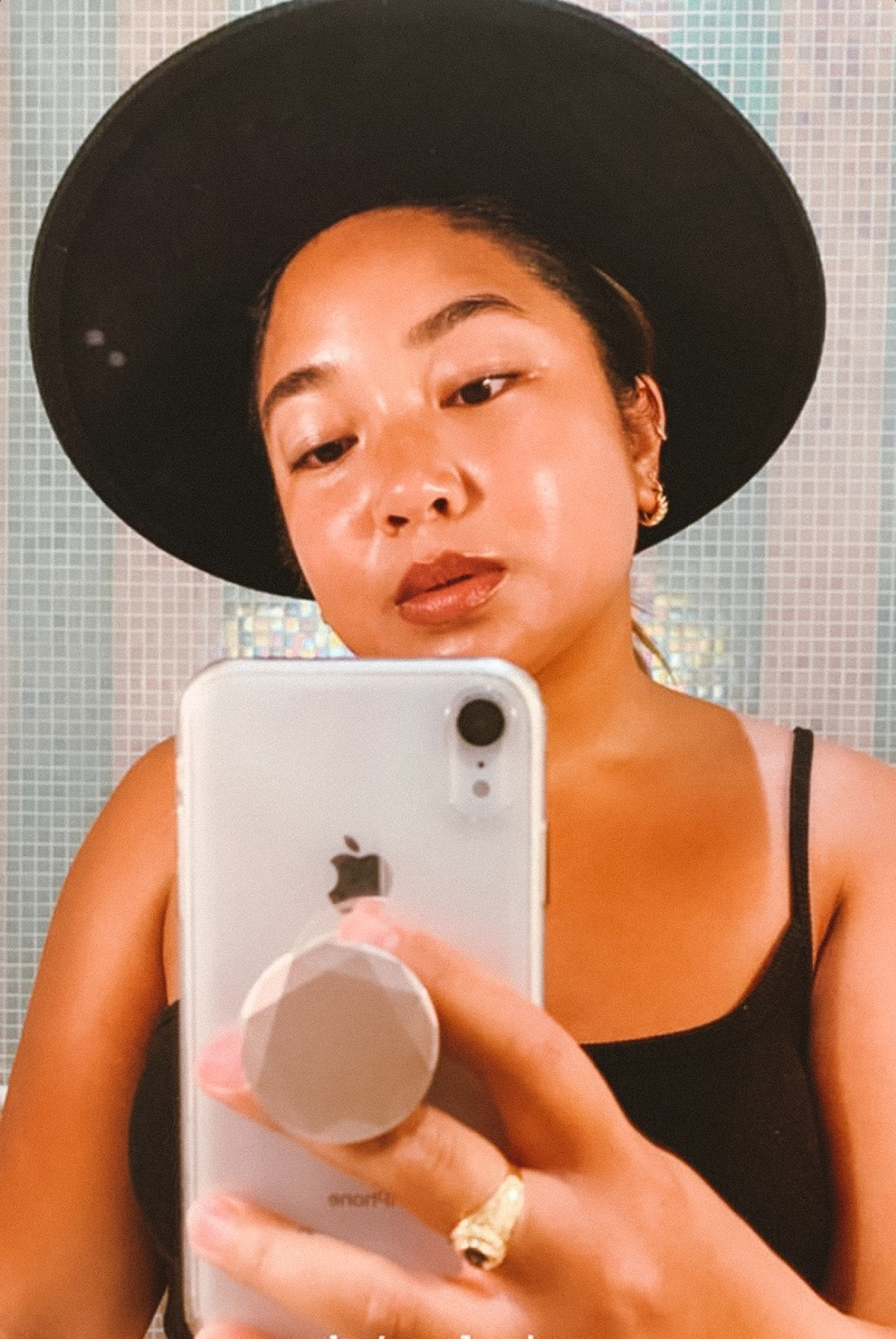 A woman in a black tank top and black hat takes a closeup phone selfie in an elevator mirror.