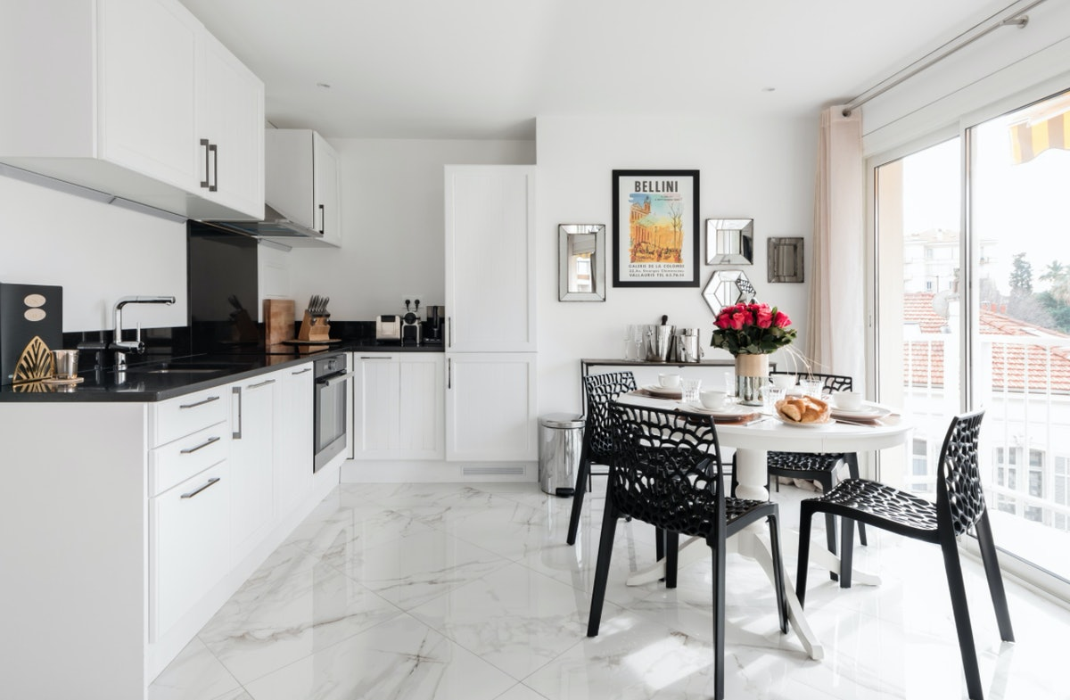 The kitchen of an apartment in Cannes is decorated with black and white details and is the perfect spot to spend a vacation.