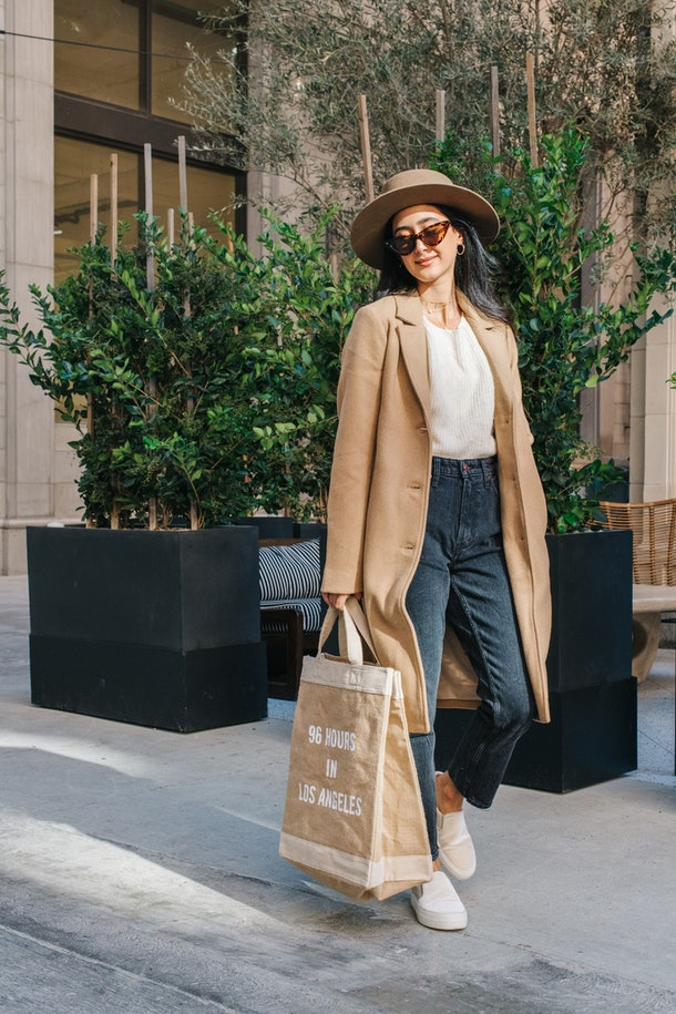 """A woman with dark hair wearing a long brown felt coat, a white sweater, dark wash jeans, and white sneakers, carrying a canvas bag that reads """"96 Hours In Los Angeles."""""""