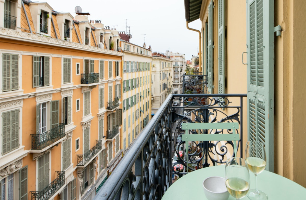 A balcony in Nice has a teal table and chairs set and overlooks orange and yellow buildings.
