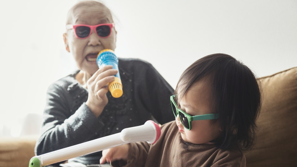 a grandmother sings on a microphone while her grandaughter plays keyboard.