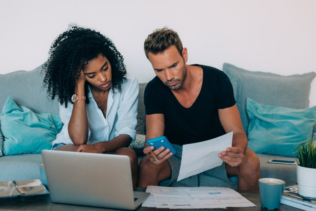 A couple looks over bills and other financial information. Saving for retirement in your 20s will increase your financial security later in life.
