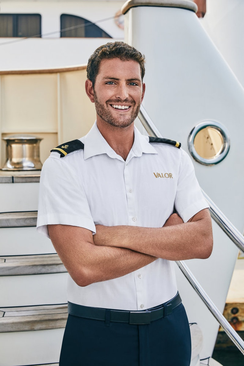 Tanner from 'Below Deck' Season 7 poses in front of a yacht.