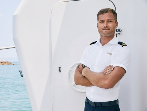 Brian De Saint Pern from 'Below Deck' poses near a yacht.