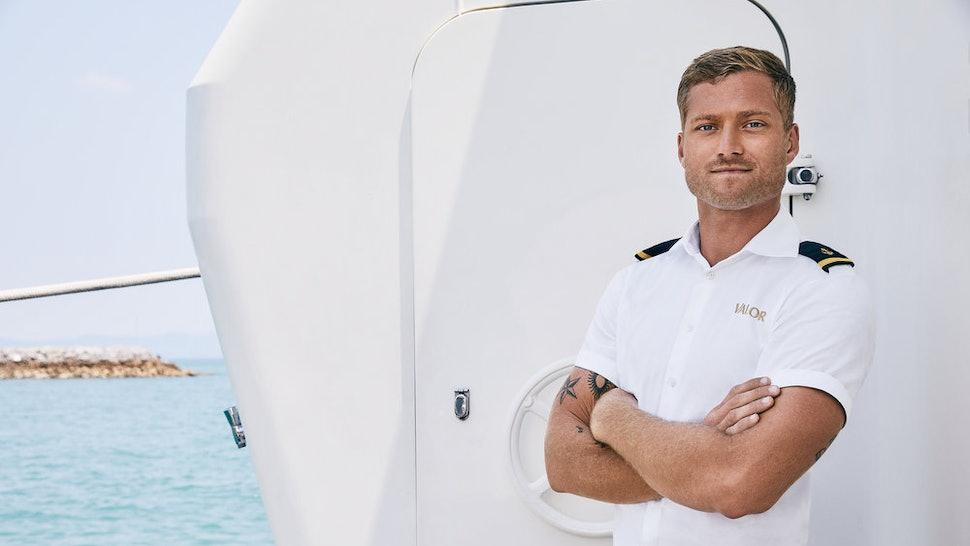 Brian De Saint Pern from 'Below Deck' poses near a yacht.