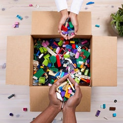box of LEGO pieces, hands holding assorted LEGO bricks