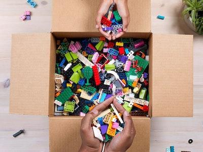 box of LEGO pieces, hands holding assorted LEGO bricks