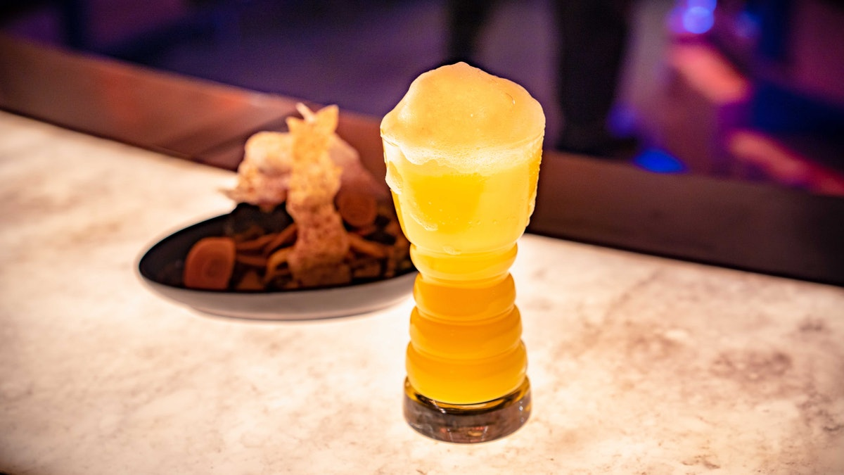 This orange drink in a cool glass is an Instagrammable Disney drink with foam on top.
