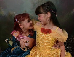Two sisters in a Belle costume and a princess costume look at each other.
