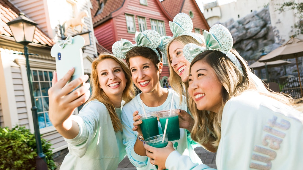 Group of women taking a selfie with aqua-colored Instagrammable Disney drinks at the theme park.