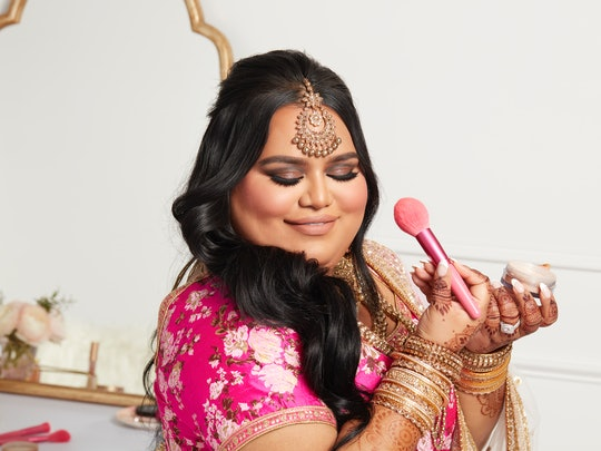 Nabela Noor poses with the Nabela Noor x e.l.f. Cosmetics collection