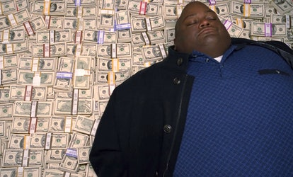Lavell Crawford in his iconic Breaking Bad pose — on top of a stack of cash.