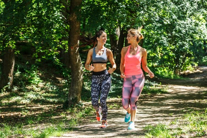 Two people in bright yoga pants run along a grassy path together, laughing. Hiring a personal trainer can be difficult, but remember that you don't have to work with the first trainer you meet.
